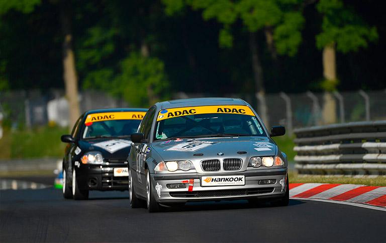 Zwei Rennwagen fahren ein Rennen in der grünen Hölle