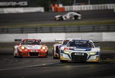 Drei Rennwagen fahren in einer Kurve auf dem Nürburgring.